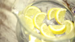 Pitcher water with ice cubes and fresh lemon