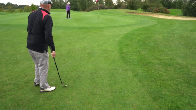 pitching onto the green as the camera spins round from front to back. - bandierina da golf video stock e b–roll
