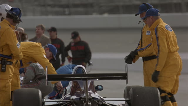 Pit-crew members work on an Indy style car by a race track as the driver stands nearby.