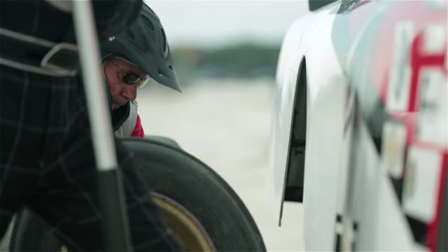 Pit-crew removes old race-car tire, replaces new tire, tightens lug-nuts, and lowers jack