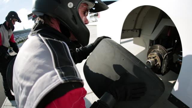 Pit-crewman replaces race-car tire