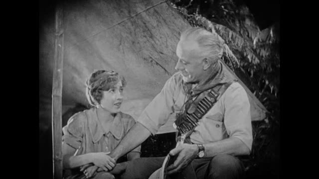 1925 pith helmeted man speaks with emotional younger woman in jungle tent - 1925 stock videos & royalty-free footage