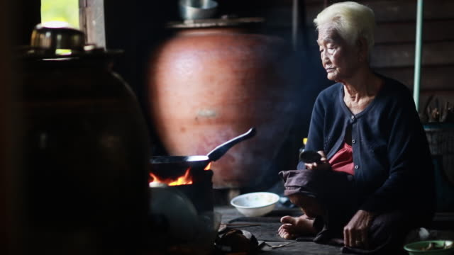 Pitiable Senior asian woman Sitting a Cooking Food