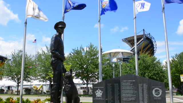 pittsburgh pennsylvania pa the new law enforcement officers enforcement memorial statue with k-9 dog and flags - figura maschile video stock e b–roll