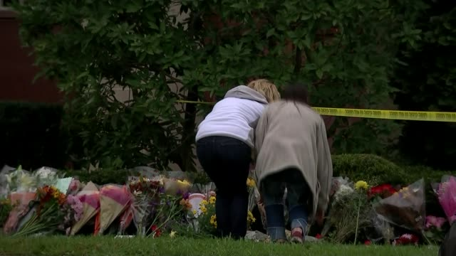 suspect charged with murder usa pennsylvania pittsburgh squirrel hill ext two women laying flowers amongst floral tributes outside tree of life... - mourning stock videos & royalty-free footage