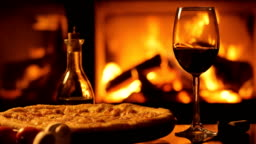 Pizza and one red wine  wineglass over fireplace background.