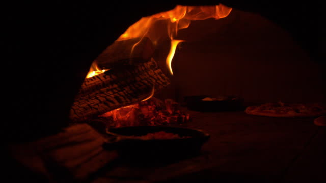 pizza baking in a wood oven, slow motion - pizza oven stock videos and b-roll footage