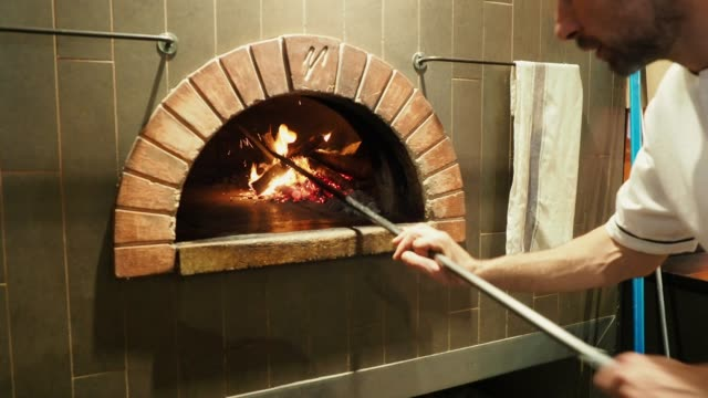 pizza chef baking a pizza in the oven - sezione parziale video stock e b–roll