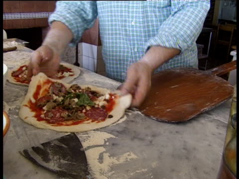 Pizza chef's hands sliding pizza onto wooden board which is then used to place pizza in tradition oven
