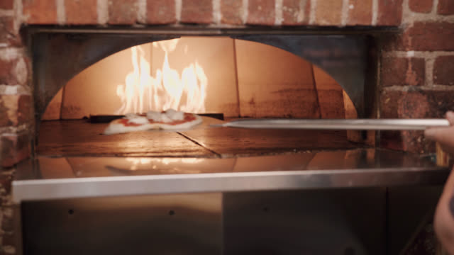 pizza in a brick oven - putting stock videos and b-roll footage