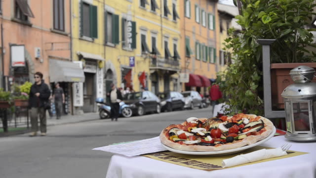 MS Pizza is on table in street restaurant / Pisa, Tuscany, Italy