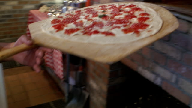 pizza maker putting pepperoni pizza in oven - hearth oven stock videos & royalty-free footage