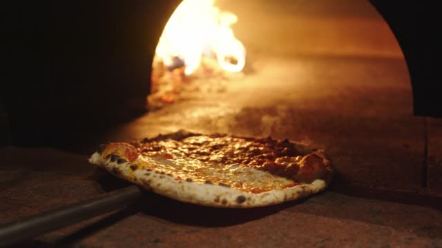 pizza maker taking the neapolitan pizza out the oven with a peel - baking stock videos & royalty-free footage