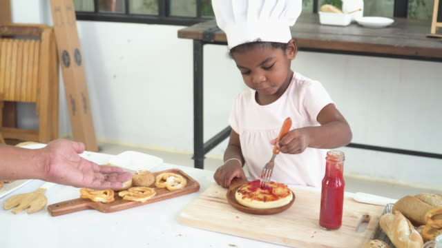 pizza preparation of a cheerful young mixed-race child between african and thai ethnic as a chef, tasting ketchup on food by herself with positive emotion, funny and smiling before serving to a customer for breakfast or lunch. concept of learning. - 2 3 years stock videos & royalty-free footage