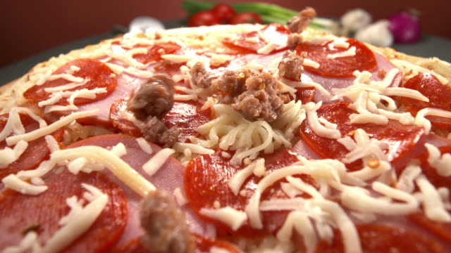 cu ts pizza sausage topping sprinkled on top of pepperoni and mozzarella on pizza crust - sausage stock videos & royalty-free footage