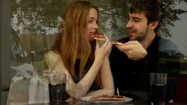 Pizza, young couple in a restaurant, window reflections.