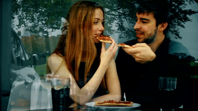 pizza, young couple in a restaurant, window reflections. - date night romance stock videos and b-roll footage