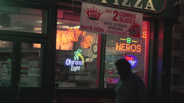 a pizzeria store front with neon signs and a people walking past.  ray's pizza. - banner sign stock videos & royalty-free footage