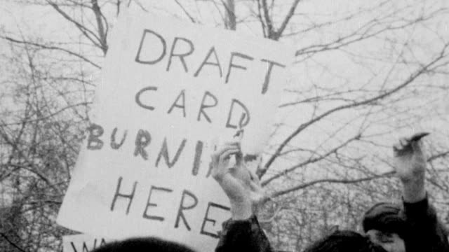 placard about draft card burning / men trying to burn draft cards / counterdemonstrators one wearing us army jacket shouting at man / placard 'end... - vietnamkrieg stock-videos und b-roll-filmmaterial