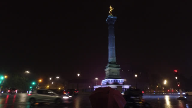 place de la bastille with only a few cars a back person with an umbrella lightning may 9 2020 in paris france - bastille stock-videos und b-roll-filmmaterial