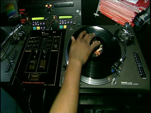 stockvideo's en b-roll-footage met dj places record on turntable and scratches record zoom in to record spinning on decks - draaitafel