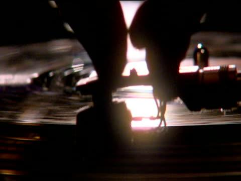 stockvideo's en b-roll-footage met dj places stylus onto rotating record - draaitafel