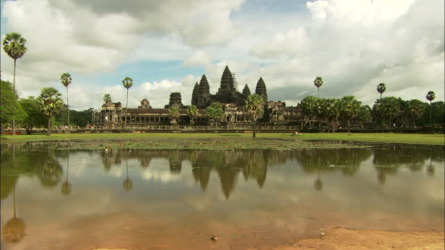 placid moat water reflects the buildings and towers of the angkor wat temple complex. - cambodia stock videos & royalty-free footage