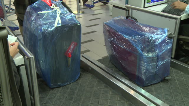 placing a plastic wrapped bag on the conveyor belt at check-in counter; airport. cape town international airport is located in cape town, south... - airport check in counter stock videos & royalty-free footage