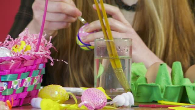 placing an easter egg in a colourful basket - korg bildbanksvideor och videomaterial från bakom kulisserna