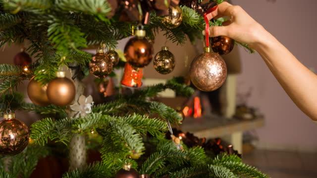 vídeos de stock, filmes e b-roll de colocando um enfeite na árvore de natal - decoração de natal