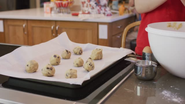 placing balls of cookie dough on baking sheet - dough stock videos & royalty-free footage