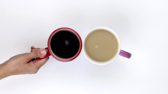 placing black coffee cup next to white coffee cup - coffee cup stock videos & royalty-free footage