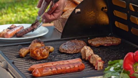 vídeos y material grabado en eventos de stock de colocar la carne a la parrilla en un plato - cocido a la parrilla