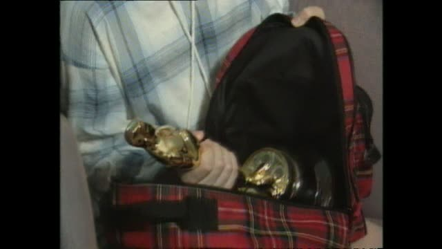 placing oscar statuette inside small tartan bag prior to being interviewed with introduction from presenter paul holmes - schottenkaro stock-videos und b-roll-filmmaterial