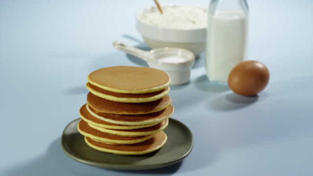 vidéos et rushes de placing pancake on top of stack of pancakes - dessert