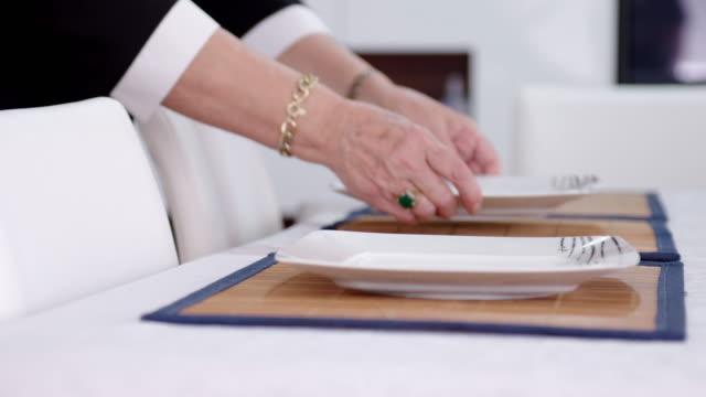 Platten auf dem gedeckten Tisch platzieren