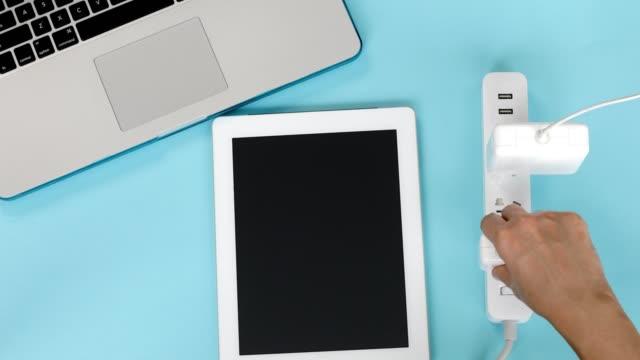 posizionamento del tablet sulla scrivania e del caricabatterie per l'alimentazione della presa - human spine video stock e b–roll