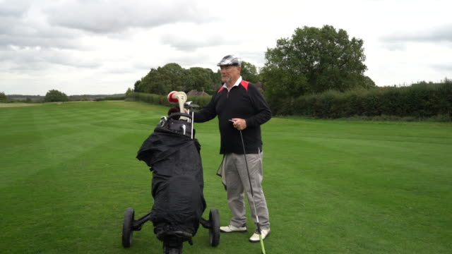 Placing the clubs back in the golf bag as the camera pans around.