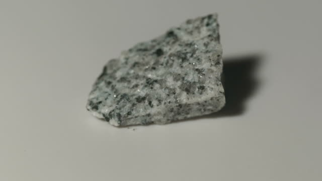 plagiogranite mineral sample in rotation with white background - igneous stock videos & royalty-free footage