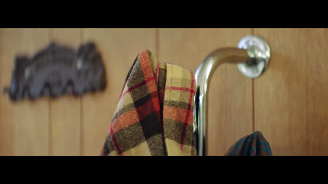 Plaid flannel shirts hang on a coat rack by a wood paneled wall in a small town barber shop.