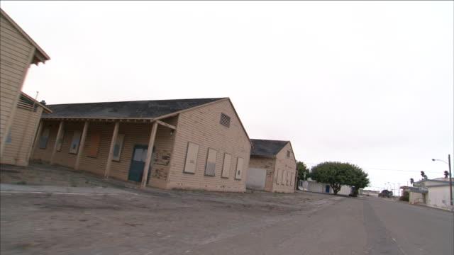 plain brick buildings face an empty street. - barracks stock videos & royalty-free footage