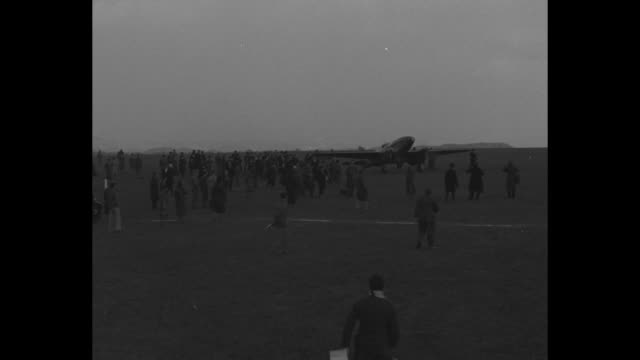 plane carrying film taxis after landing at airfield near london small crowd on airfield / closer view of plane taxiing people surrounding it / pilot... - 1934 bildbanksvideor och videomaterial från bakom kulisserna