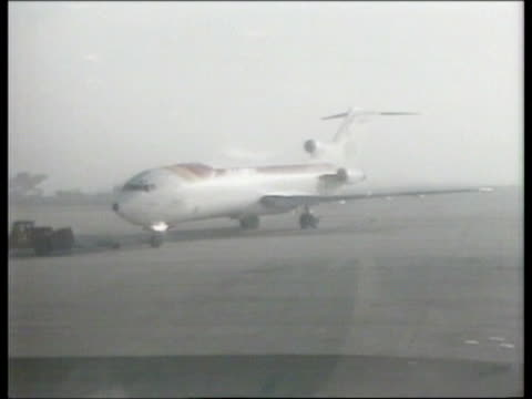 Aftermath ITN SPAIN Madrid Barajas Airport GV 727 plane towed TOWARDS seen through mist INT GV People in terminal