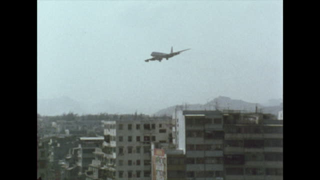 plane comes into land at kai tak airport; 1972 - vergangenheit stock-videos und b-roll-filmmaterial