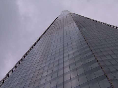 plane flies above the shard europe's tallest building - shard london bridge stock videos & royalty-free footage