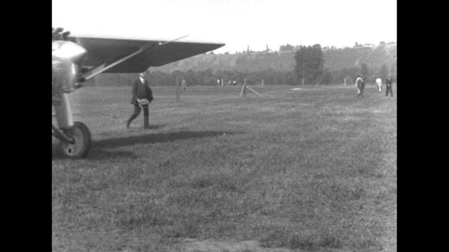 plane flies low over airport / plane taxis across field / plane comes to stop three men approach door of cockpit policeman standing in foreground /... - charles lindbergh stock videos & royalty-free footage