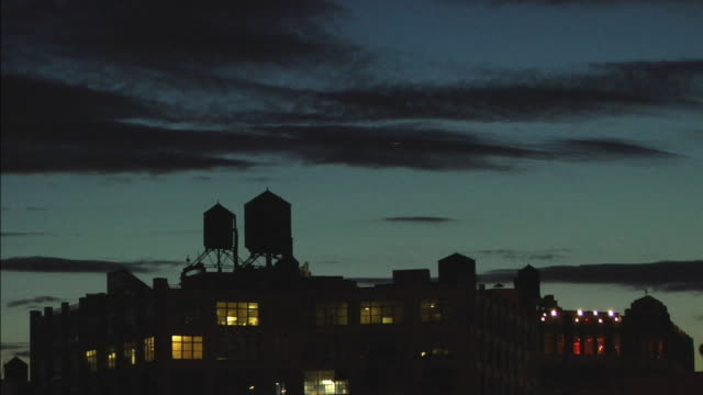 slo mo ha ws plane flying above water towers atop roof in williamsburg at night / brooklyn, new york, usa - brooklyn new york stock videos & royalty-free footage