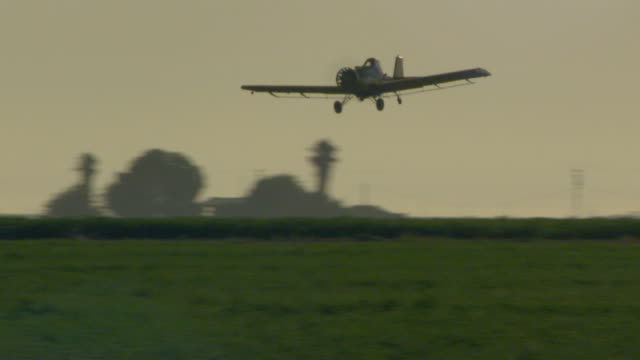 plane flying over field - insecticide stock videos & royalty-free footage