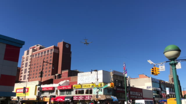 plane flying over flushing chinatown in queens, new york - flushing queens stock videos and b-roll footage