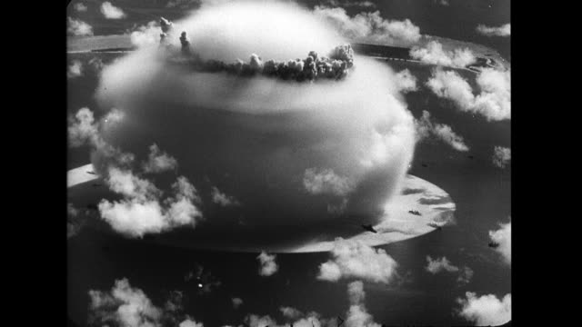 plane flying overhead undersea atomic explosion wilson cloud rising and dissipating as the waves created envelope ships placed around the bomb site - atomic bomb testing stock videos & royalty-free footage